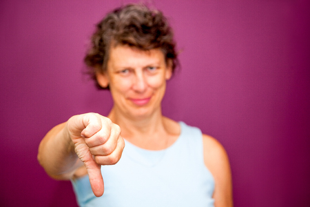 Displeased woman showing thumb down Stock Photo