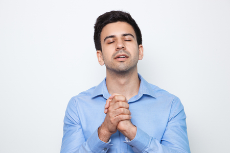 Young Attractive Man Praying With Clasped Hands