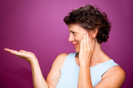 Pretty senior woman pointing aside Stock Photo
