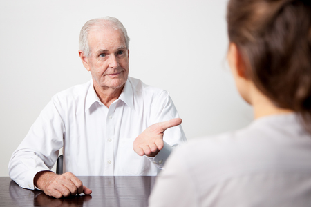 Positive senior man interviewing candidate Stock Photo