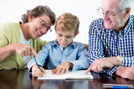 three generations of women: Diligent Grandson Doing Homework With Grandparents Stock Photo