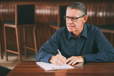 Thoughtful Senior Man Writing Notes in Restaurant