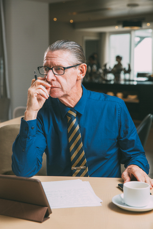 Thoughtful Senior Businessman Working in Cafe Stock Photo