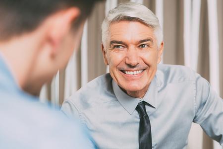 Smiling Senior Businessman Talking to Partner