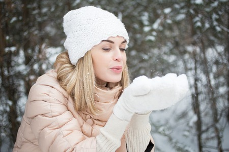 christmas spending: Carefree woman blowing snow off hands