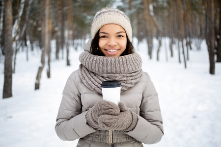 Happy African woman with coffee cup in winter