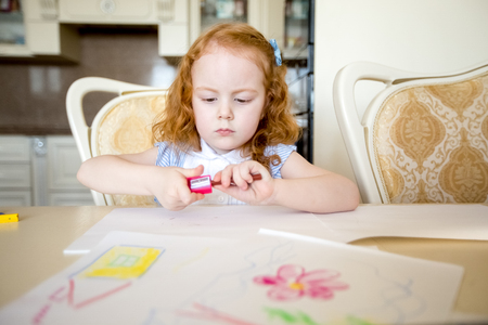 Pequeña muchacha seria de la redhead que afila el lápiz