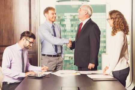 Twee zakenlieden glimlachend en handen schudden Stockfoto - 73903480