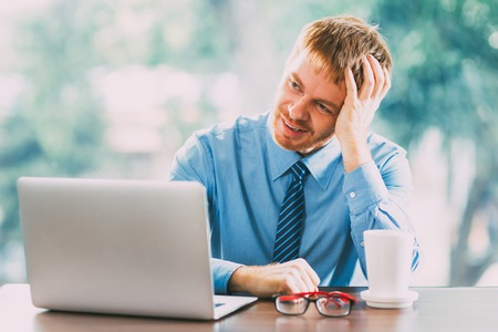 Young Businessman Thinking over Idea in Office Stock Photo