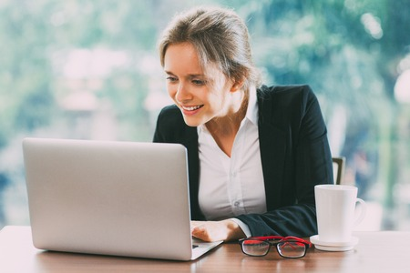 Young Smiling Businesswoman Working on Laptop