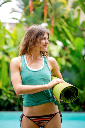 Serene young woman with exercise mat outdoors