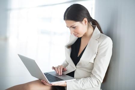 Beautiful Business Woman on Floor Working on Laptop