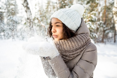 Portrait of happy girl blowing snow in winter Stock Photo