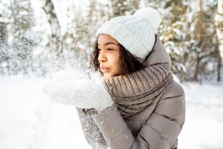 Portret van gelukkige meisjes blazende sneeuw in de winter