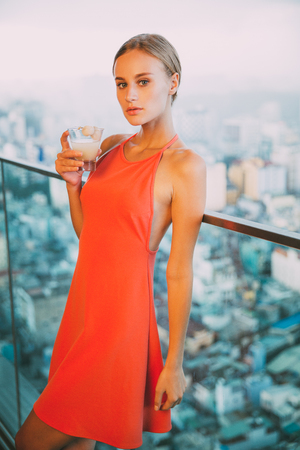 baranda para balcon: Young Woman Standing on Balcony with Cocktail