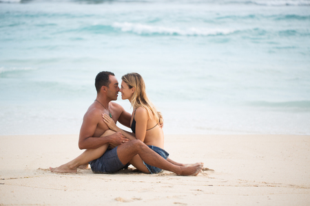 Affectionate couple sitting on sand