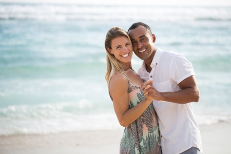 mixed marriage: Just married couple embracing on beach