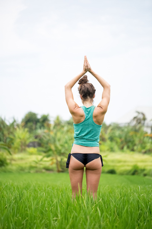 Back View Of Woman Doing Yoga on Summer Meadow Stock Photo