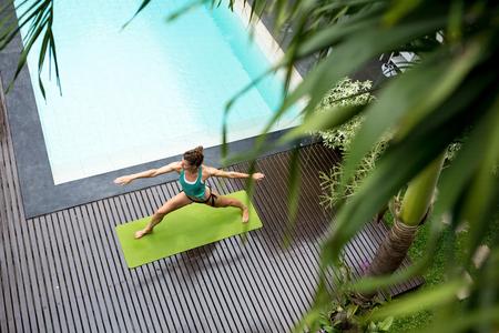 Woman Doing Yoga Warrior Pose in Swimming Pool