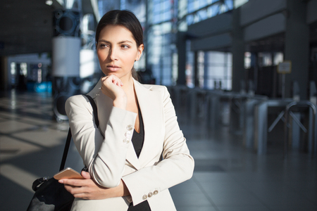 Contemplative businesswoman touching chin in lobby Stock Photo