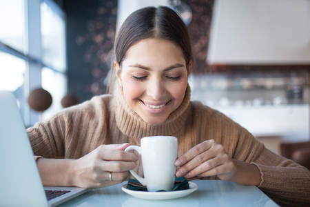 caffeine free: Positive woman enjoying smell of coffee
