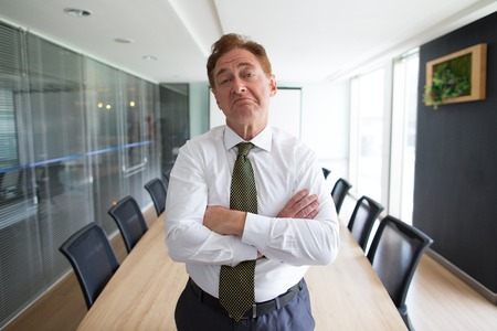 Sceptische hogere zakenman die zich in bestuurskamer bevindt Stockfoto