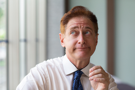 skeptical: Sceptical businessman looking up