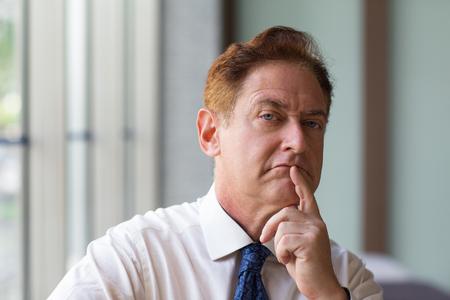Stern mature employer touching chin Stock Photo