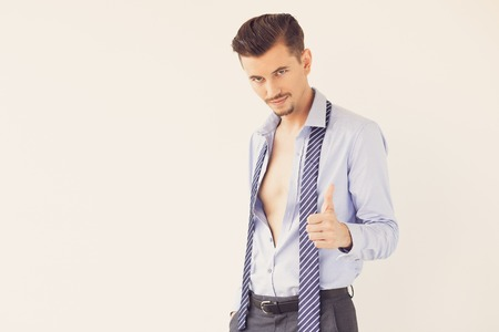 Young Man in Unbuttoned Shirt Showing Thumb Up Stock Photo