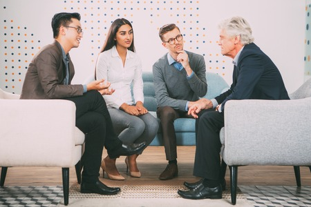 couching: Young People Talking to Senior Business Leader Stock Photo