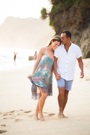 Smiling couple walking alone beach and talking