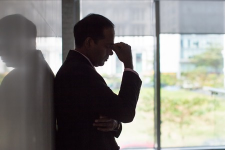 tired businessman: Silhouette of stressed businessman rubbing eyes Stock Photo