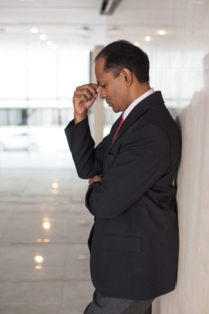 tired businessman: Stressed mid adult Indian businessman rubbing eyes Stock Photo