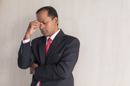 overworking: Tired businessman rubbing eyes standing at wall Stock Photo
