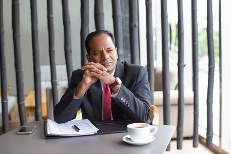 businessman pondering documents: Pensive Business Man Working With Document in Cafe