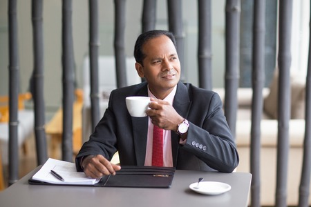 businessman pondering documents: Thoughtful Business Man Drinking Coffee in Cafe