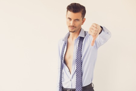 Young Man in Unbuttoned Shirt Showing Thumb Down