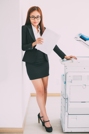 Pretty Asian Business Woman Standing at Copier Stock Photo