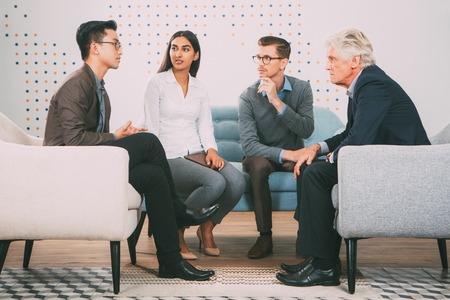 couching: Serious People Talking to Senior Business Leader Stock Photo