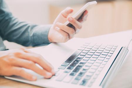 media gadget: Businessman texting message sitting at laptop