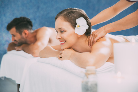 Happy Woman Getting Massage and Man in Background Stock Photo