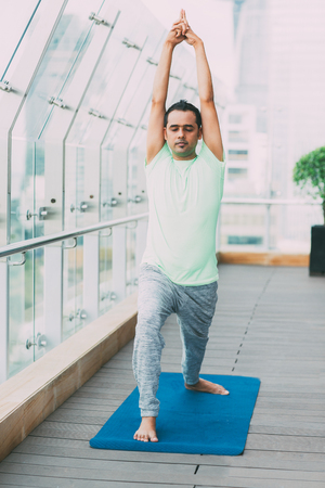 closed club: Man Doing Yoga Warrior Pose in Fitness Center