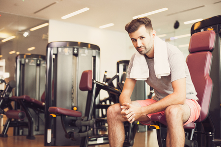 keeping room: Tired young man relaxing on weight machine in gym
