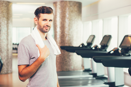 keeping room: Smiling young man portrait in gym Stock Photo