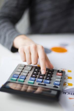 Closeup of Hand Pushing Button on Calculator