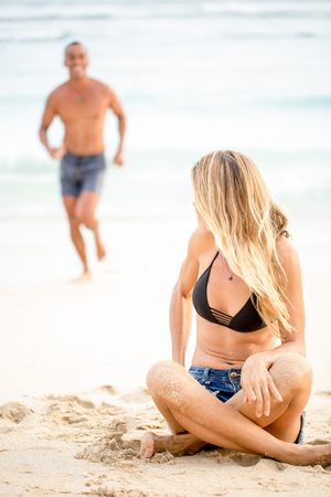 Happy woman sitting on sand and looking at her man