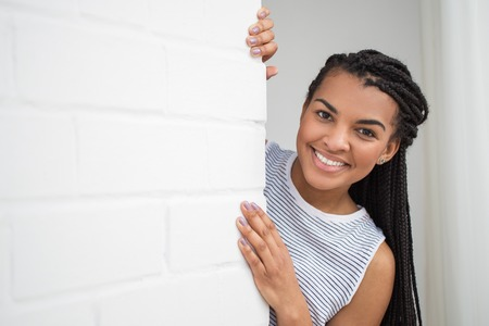 Happy Black Woman Peeping From Behind Wall Stock Photo