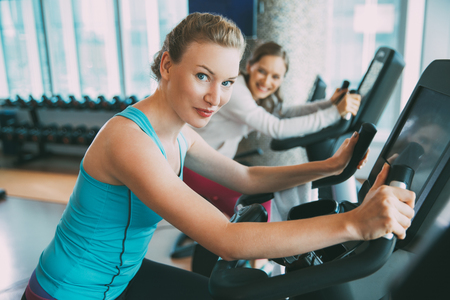Young Woman Cycling Exercise Bike in Fitness Club