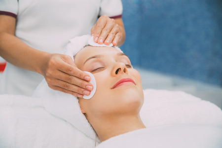 Young Woman Getting Facial Treatment in Spa Salon Stock Photo