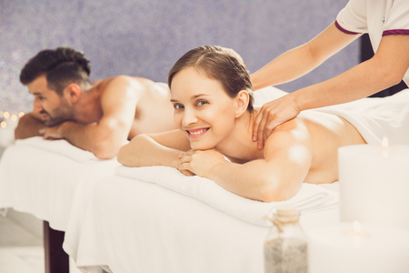 Woman Getting Back Massage with Man in Background